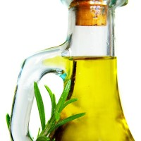 Closeup of olive oil and rosemary, isolated on white